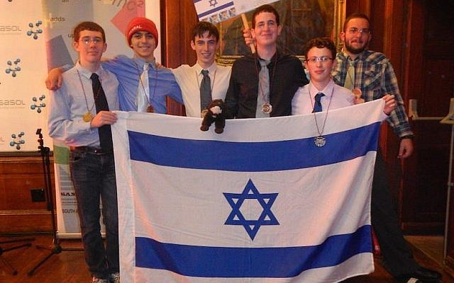 (L to R, holding the flag) Team members Tomer Novikov, Dor Shmoish, Nitzan Tor, David Metzer, Amotz Oppenheim, Omri Solan. Background right: Lev Radizolonsky, team coach (Photo credit: Courtesy)