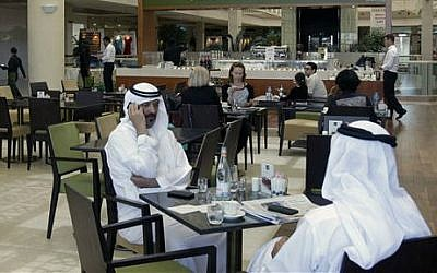 In this Wednesday, May 21, 2014 photo, Emirati and other customers enjoy their free time at the Bateel Cafe in Dubai, United Arab Emirates (photo credit: AP/Kamran Jebreili)