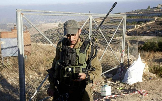 An Israeli soldier patrols near the area where the bodies of three Israeli teenagers were found, in the village of Halhul, near the West Bank city of Hebron, Tuesday, July 1, 2014. (photo credit: AP/Majdi Mohammed)