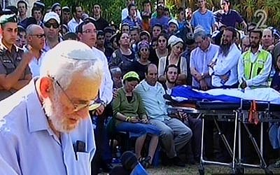 The grandfather of Naftali Fraenkel speaking at his funeral while his bodies lies draped in an Israeli flag in front of his parents in Nof Ayalon Tuesday. (Screen capture: Channel 2)