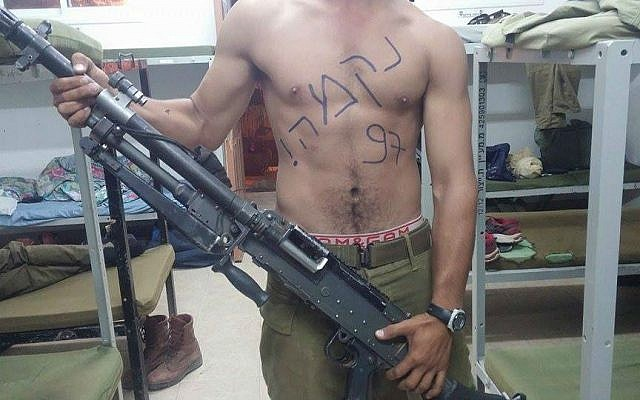 "A soldier poses with a machine gun. The word ""revenge"" is written on his chest, along with ""97,"" a possible reference to the 97th light infantry battalion of the Kfir Brigade, which operates in the West Bank. (photo credit: ""The Nation of Israel Demands Vengeance!"" Facebook page)"
