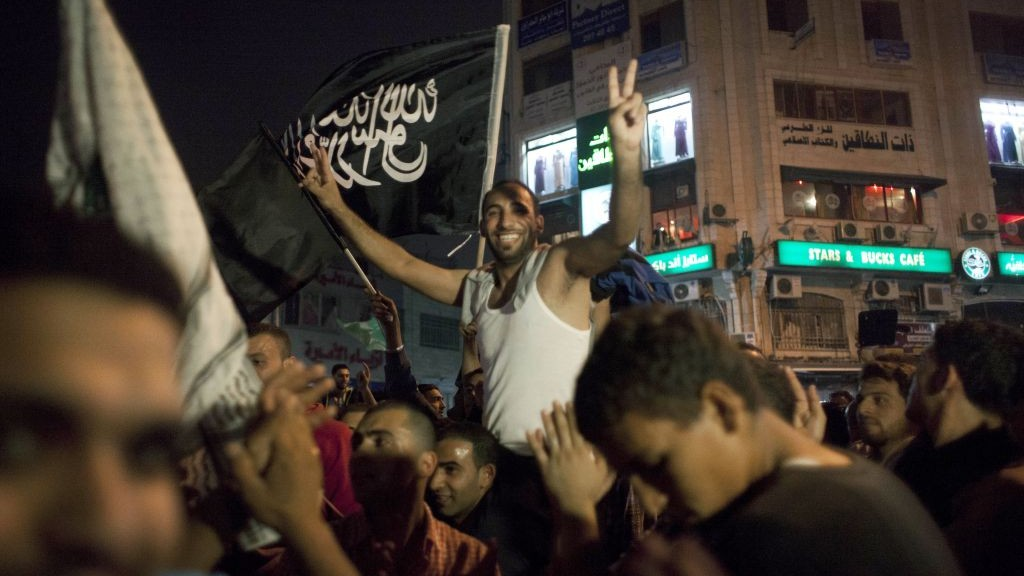 "Palestinians dance while flying a Palestinian Islamic Jihad Movement flag reading in Arabic ""there is only one God and Muhammad is his prophet,"" during celebrations in the West Bank city of Ramallah, late Sunday, July 20, 2014.  (photo credit: AP Photo/Nasser Nasser)"