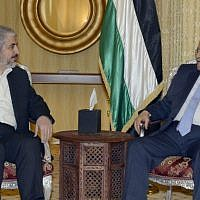 A handout picture released by the Palestinian Authority president's office shows Mahmoud Abbas (right) in a meeting with the head of the political bureau of Hamas, Khaled Mashaal, in Doha, on July 20, 2014. (AFP/PPO/Thaer Ghanem)