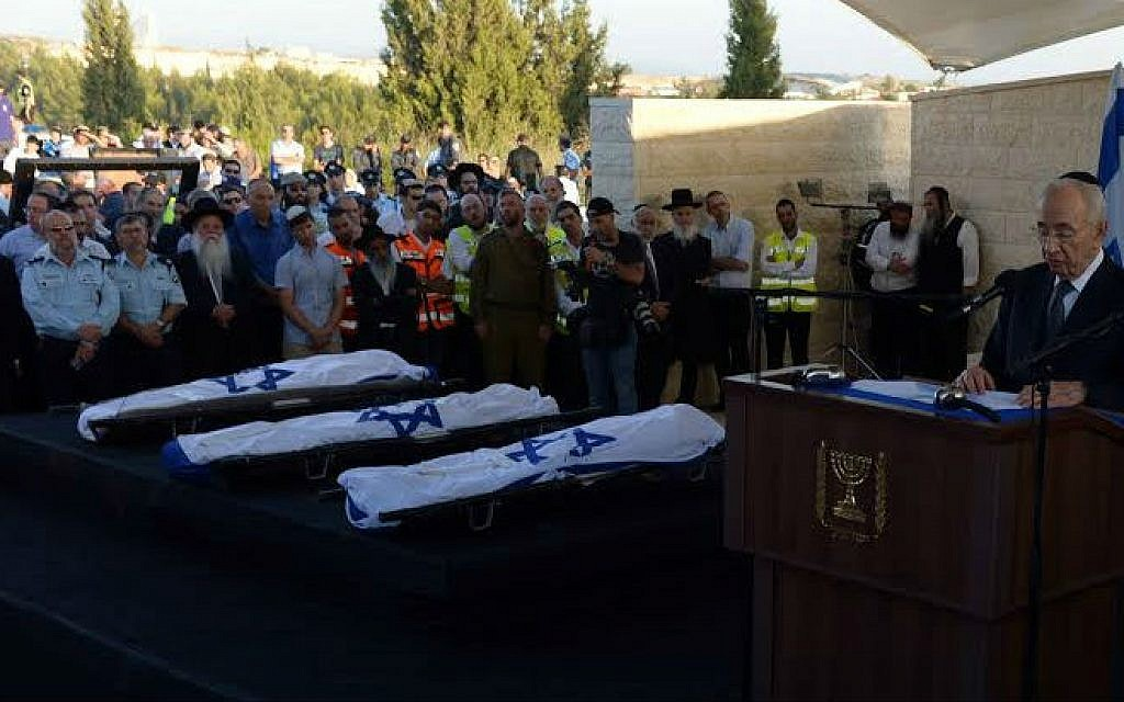 President Shimon Peres delivering a eulogy next to the flag-draped bodies of Naftali Fraenkel, Gil-ad Shaar and Eyal Yifrach at their funeral July 1, 2014 (photo credit: Chaim Tzach)