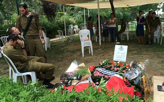 Friends and fellow soldiers at Yuval Heiman's gravesite after his funeral on Tuesday. (Courtesy)