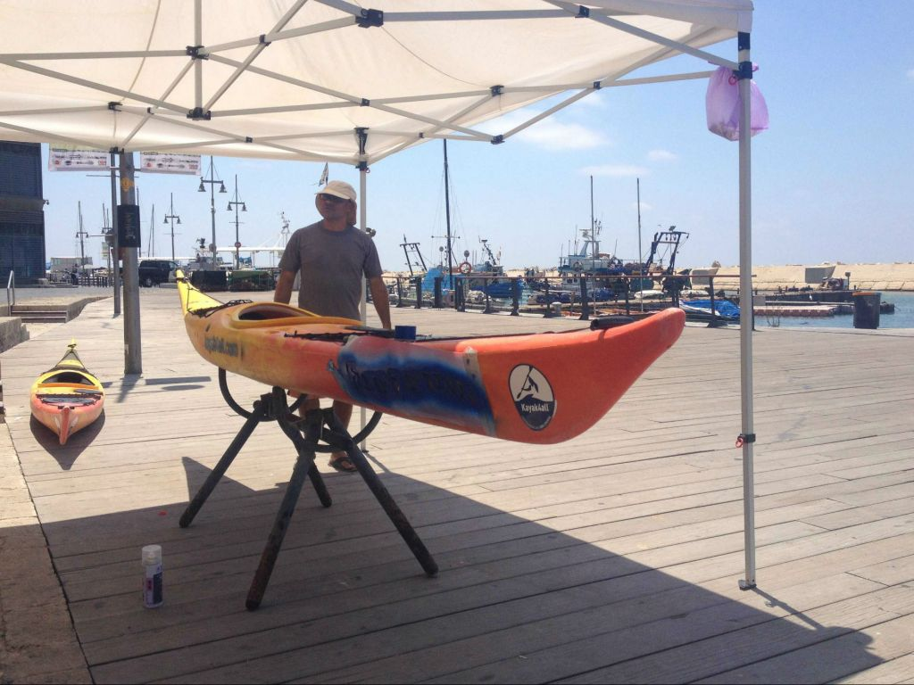 Kayak instructor Roni Levinson is stuck painting his kayaks rather than taking customers out on the water (photo credit: Jessica Steinberg/Times of Israel)