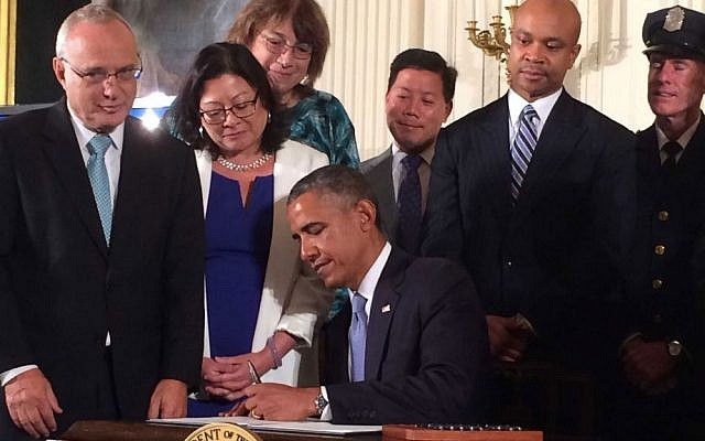 President Barack Obama signs an executive order extending work protection rights to LGBT employees of federal contractors, as Rabbi David Saperstein (left), director of the Religious Action Center of Reform Judaism, looks on, at the White House, on July 18, 2014. (photo credit: Hadar Susskind/Bend the Arc via JTA)