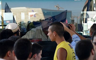 Protesters bang on a bus and put stickers that call for 'revenge' in front of its Arab bus driver during a large protest in central Jerusalem, on July 1, 2014 (photo credit: Mendy Hechtman/Flash90)