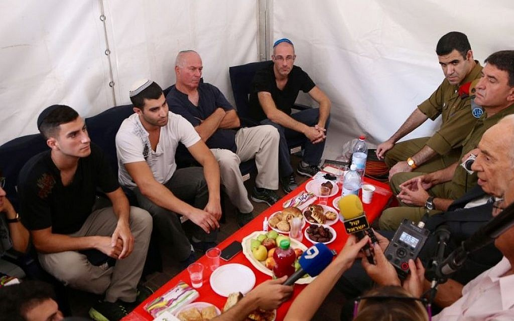 Israeli president Shimon Peres meets with the family of IDF (Israel Defense Force) Sgt. Bnaya Rubel, 20, in their home in the central Israeli town of Holon, on July 20, 2014.  (photo credit: FLASH90)