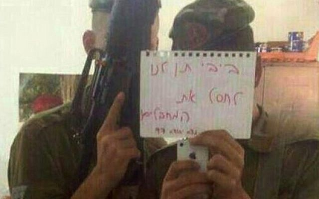 IDF soldiers pose with a sign reading 'Bibi, let us assassinate the terrorists.' (photo credit: Channel 2 via Facebook)