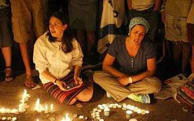 In this June 30, 2014 photo, citizens are seen lighting candles at the hitchhiking site in the West Bank from where three young Jewish teenagers, Eyal Yifrach, Naftali Fraenkel and Gilad Sha'ar were abducted on June 12 (photo credit: Jonathan Sindel/Flash90)