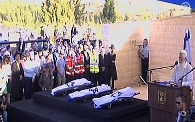 Rabbi Dov Zinger, head of the Mekor Haim yeshiva, delivering a eulogy next to the flag-draped bodies of Naftali Fraenkel, Gil-ad Shaar and Eyal Yifrach at their funeral Tuesday. (Screen capture: Channel 2)