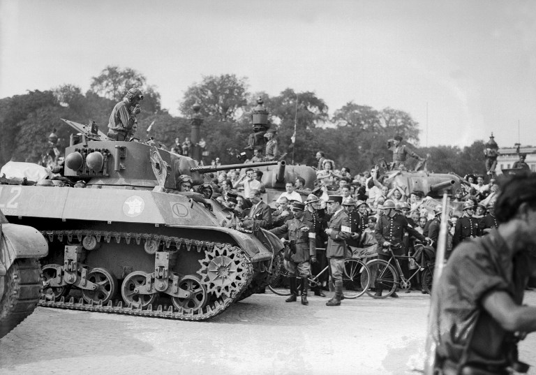 The crowd, flanked by firemen, greets a tank of the Leclerc Division during the military parade, on August 26, 1944 , Place de la Concorde, the day after the Liberation of Paris. (photo credit: AFP/File)