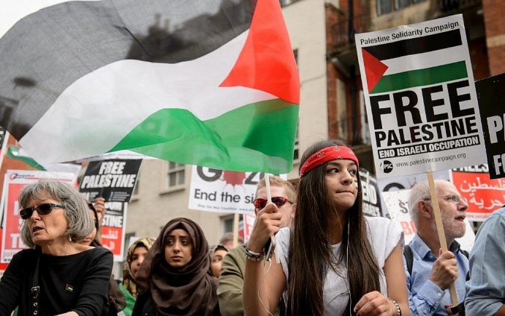 A demonstrator waves the Palestinian flag during a protest near the Israeli embassy in central London on Friday, August 1, 2014, calling for an end to Israel's military offensive in the Gaza Strip. (photo credit: Leon Neal/AFP)