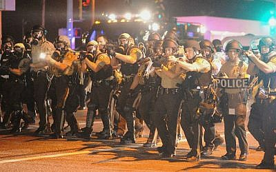 Law enforcement officers watch on during a protest on West Florissant Avenue in Ferguson, Missouri on August 18, 2014. (photo credit: AFP/Michael B. Thomas)