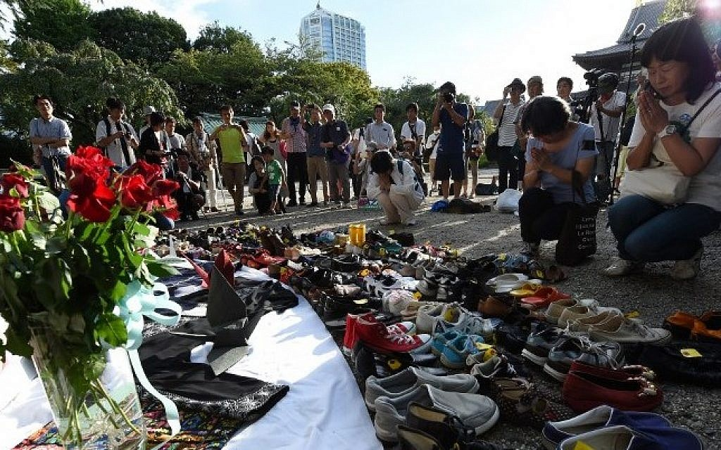 People pray for Palestinian victims, especially some 480 children, killed by Israeli strikes in Gaza after placing shoes in front of a temporary altar at Jozoji temple in Tokyo on August 23, 2014. More than 100 people gathered to pray for peace between Palestine and Israel (Photo credit: Toru Yamanaka/AFP)
