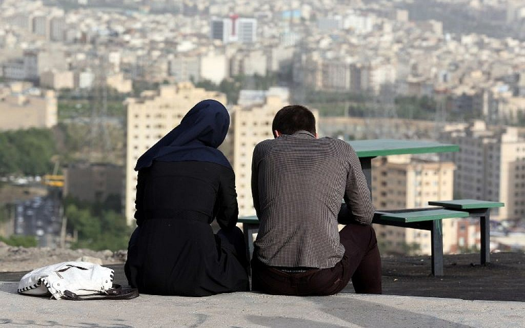 An Iranian couple sit together in the northwestern Shahran neighborhood  overlooking Tehran on June 7,