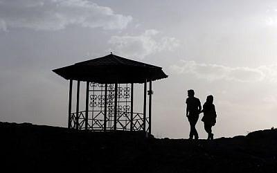 An Iranian couple walk together in the northwestern Shahran neighbourhood overlooking Tehran on June 7, 2014. (photo credit: AFP Photo/Atta Kenare)