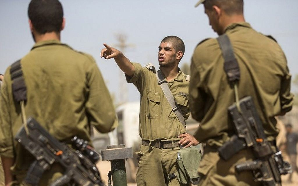 Israeli soldiers take part in a briefing at an army deployment area on the southern Israeli border with the Gaza Strip Friday, August 1, 2014. (photo credit: Jack Guez/AFP)