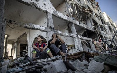 Palestinian brothers sit on the rubble of their house in front of an apartment block in part of the northern Beit Hanoun district of the Gaza Strip on August 5, 2014. (photo creditAFP/MARCO LONGARI)