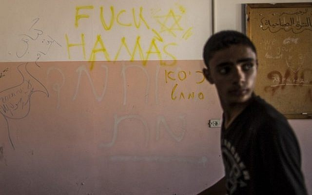 A Palestinian boy walks past writing on a wall allegedly left behind by Israeli soldiers who used the Beit Hanun High school for girls as an advanced base during its military offensive against the Hamas-held Gaza Strip, on August 5, 2014. (photo credit: Marco Longari/AFP)