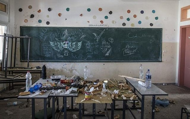 Leftover food seen in a classroom where a military crest and some graffiti in Hebrew are seen on a blackboard after Israeli soldiers withdrew from the Beit Hanun High school for girls, which was reportedly used as an advanced base during Israel's military offensive against the Hamas-held Gaza Strip, on August 5, 2014. (photo credit: Marco Longari/AFP)