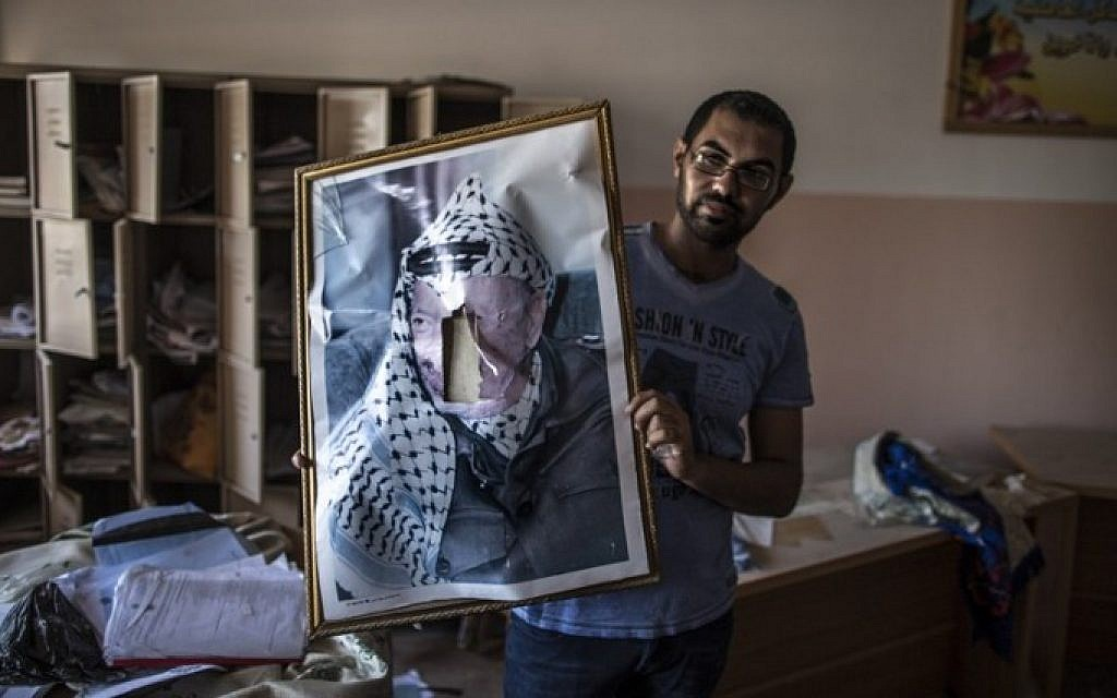 A defaced portrait of the late Palestinian leader Yasser Arafat is held by a man in a classroom after Israeli soldiers withdrew from the Beit Hanun High school for girls which was reportedly used as an advanced base during Israel's military offensive against Hamas, on August 5, 2014 (Photo credit: Marco Longari/AFP)