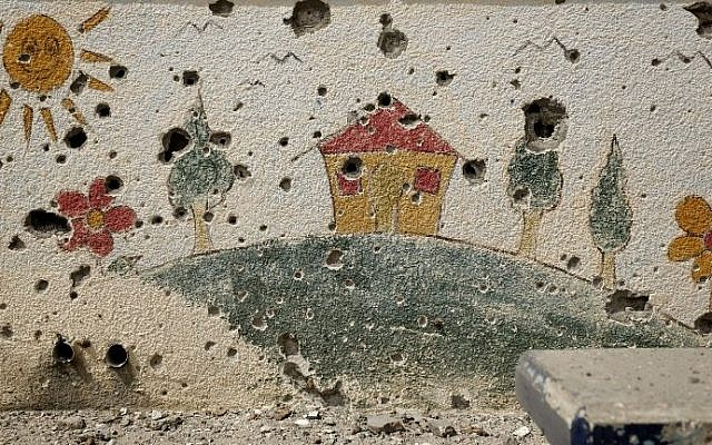 Shrapnel holes are seen on a decorated wall in the heavily damaged Sobhi Abu Karsh school in Gaza City's Shejaiya neighborhood on Tuesday, August 5, 2014. (photo credit: Mohammed Abed/AFP)