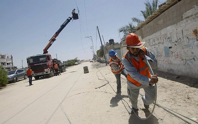 Palestinian electricity company workers drag a power line, many of which were destroyed following an Israeli airstrike in Rafah in the southern Gaza Strip, on August 6, 2014. (photo credit: AFP/SAID KHATIB)