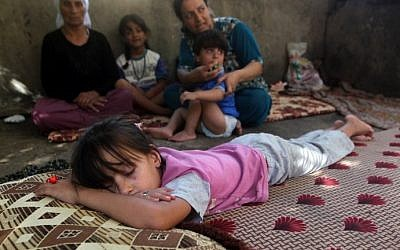 A child sleeps as Iraqi Yazidis, who fled their homes when Islamic State militants attacked the town of Sinjar, sit in a building where they found refuge  in the Kurdish city of Dohuk in Iraq's autonomous Kurdistan region, August 10, 2014. (photo credit: AFP/Ahmad al-Rubaye)