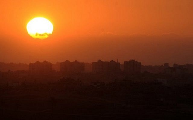 A picture taken at sunset on August 10, 2014 shows buildings in the northern Gaza Strip from the Israeli side of the Israel-Gaza Border (Photo credit: David Buimovitch/AFP)