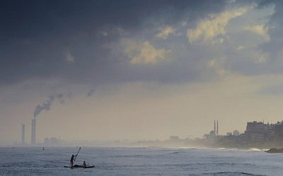 Illustrative photo of Palestinian fishermen paddling their small boat a few hundred meters off the beach of Gaza City while casting their nets in search of small fish on August 10, 2014. (photo credit: AFP/Roberto Schmidt)