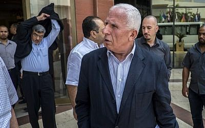 Palestinian Fatah delegation chief Azzam al-Ahmed, center, and members of the Palestinian Fatah delegation leave the hotel where the negotiations are taking place with Egyptian intelligence mediators aimed at brokering an end to the Gaza conflict on August 12, 2014 in the Egyptian capital, Cairo. (photo credit: AFP/KHALED DESOUKI)