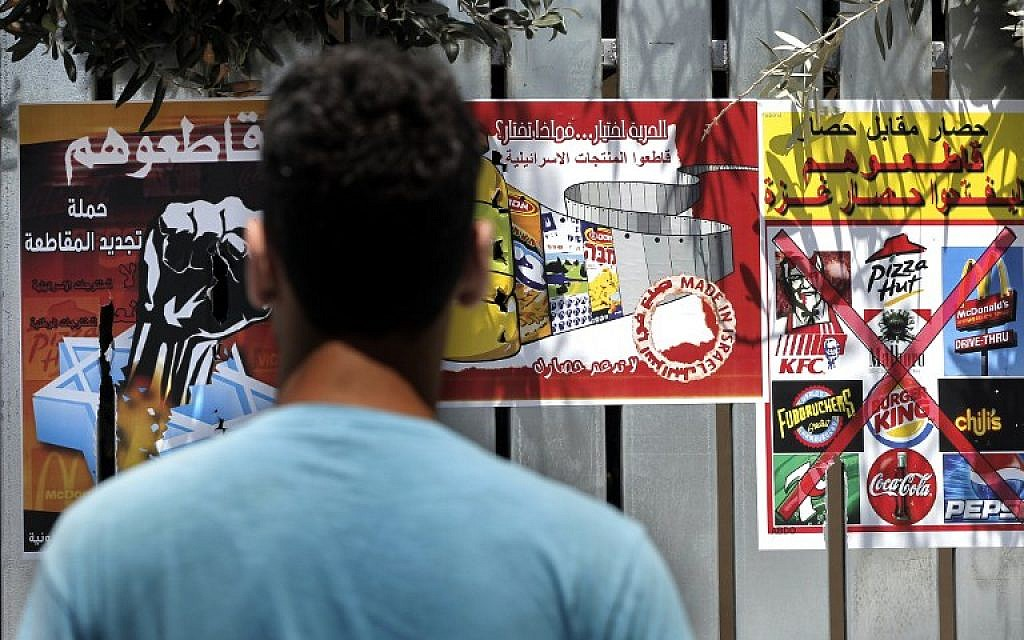 "A Palestinian man reads posters calling people to boycott Israeli products and other companies following the latest war between Hamas militants in the Gaza Strip and Israel's army, on August 12, 2014 in the mostly Arab East Jerusalem . The posters read from L to R: ""Boycott them, the campaign for a renewing boycott"", ""Freedom is a choice, what do you choose?"", ""Blockade for blockade, boycott them, until they lift the Gaza blockade"". (photo credit: AFP/AHMAD GHARABLI)"