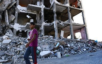Feras Abu Inil, 13, walks past an apartment block in the northern Gaza strip that was all but destroyed in four weeks of clashes between Israel and Hamas, Wednesday, August 13, 2014. (photo credit: Roberto Schmidt/AFP)