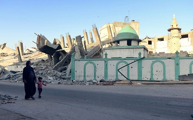 A Palestinian woman and a child walk past the destroyed Omari mosque on August 12, 2014 in Jabaliya, northern Gaza Strip. (photo credit:  AFP PHOTO/ROBERTO SCHMIDT)