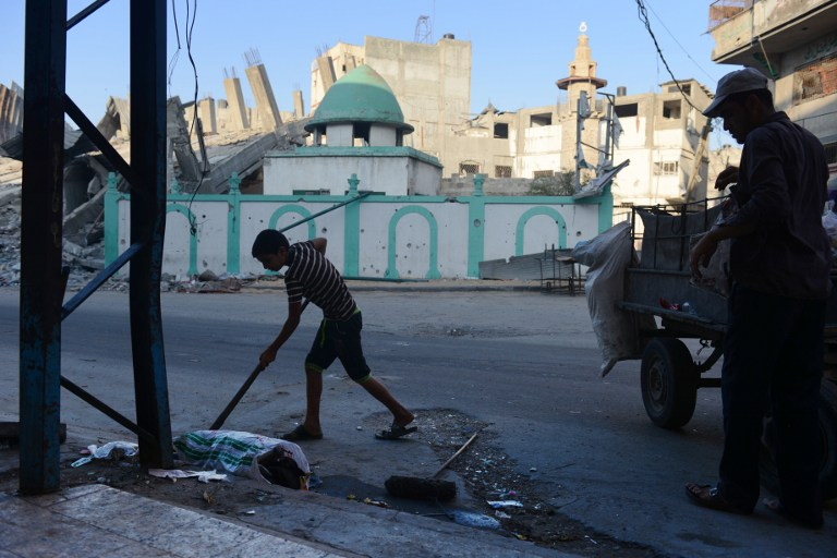 A Palestinian boy and his father clean garbage in the street across from the Omari mosque on August 12, 2014 in Jabalia, in the northern Gaza Strip. (photo credit: AFP/ROBERTO SCHMIDT)