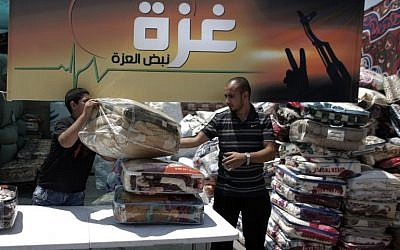 Palestinians collect goods and blankets in East Jerusalem, on Thursday, August 14, 2014, to be sent and distributed with the Red Cross to people in need in the Gaza Strip (photo credit: AFP/AHMAD GHARABLI)