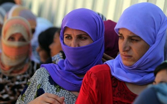 Yazidi Iraqi women queue in order to get food at the Bajid Kandala camp near the Tigris River, in Kurdistan's western Dohuk province, where they took refuge after fleeing advances by Islamic State jihadists in Iraq on August 13, 2014. Photo credit:AFP/AHMAD AL-RUBAYE)