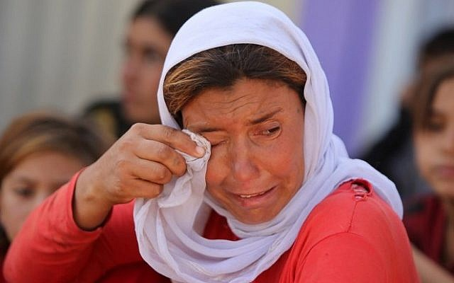 A displaced Iraqi Yazidi woman wipes her eyes at the Bajid Kandala camp near the Tigris River, in Kurdistan's western Dohuk province, where they took refuge after fleeing advances by Islamic State jihadists in Iraq on August 13, 2014. (Photo credit:AFP/AHMAD AL-RUBAYE)
