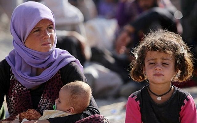 File: A Yazidi Iraqi woman sits with her children at the Bajid Kandala camp near the Tigris River, in Kurdistan's western Dohuk province, where they took refuge after fleeing advances by Islamic State jihadists in Iraq on August 13, 2014. (AFP/Ahmad Al-Rubaye)