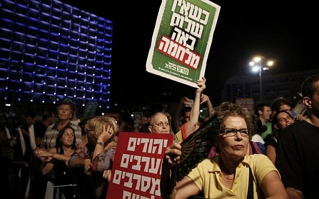 A demonstrator holds up placards reading, in Hebrew, 'When there is no peace war comes' (top) and 'Jews and Arabs refuse to be enemies' (bottom), as thousands of Israelis protest during a left-wing peace rally in Tel Aviv calling for the Israeli government to negotiate with the Palestinian Authority, on Saturday, August 16, 2014 (photo credit: AFP/GALI TIBBON)