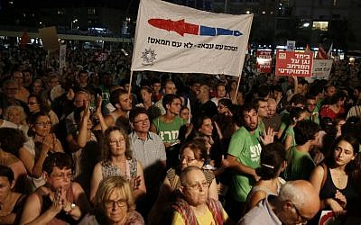 "Demonstrators hold a placard reading in Hebrew: ""Agreement with Abbas not with Hamas"" as thousands of Israelis protest during a left-wing peace rally in the coastal city of Tel Aviv calling for the Israeli government to negotiate with the Palestinian Authority on August 16, 2014. (photo credit:AFP/GALI TIBBON)"