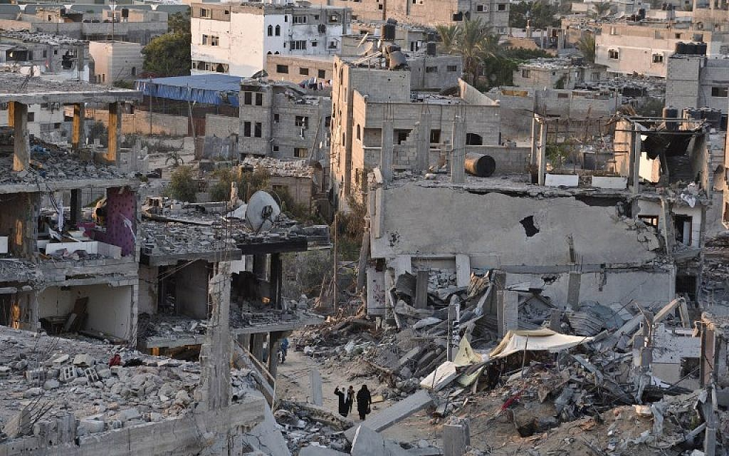 Palestinian women walk between buildings destroyed during fighting between Hamas militants and Israel in the Al-Shaas neighbourhood, in the north of the Gaza Strip, on August 16, 2014. (photo credit: AFP/ROBERTO SCHMIDT)