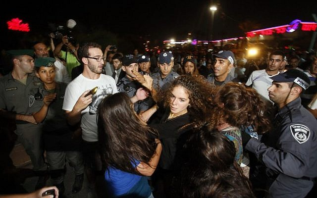 An Israeli supporter of the right-wing Organization for Prevention of Assimilation in the Holy Land (LEHAVA) scuffles with police during a demonstration outside the wedding hall where Mahmoud Mansour, an Arab-Israeli, and Morel Malka, born Jewish, got married on August 17, 2014 in Rishon Letzion. (photo credit:AFP/GALI TIBBON)