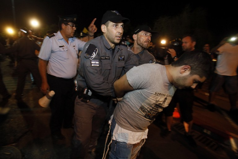 An Isaeli supporter of the right-wing Organization for Prevention of Assimilation in the Holy Land (LEHAVA) is detained by police during a demonstration outside the wedding hall where Mahmoud Mansour, an Arab-Israeli, and Morel Malka, born Jewish, got married on August 17, 2014. (photo credit: AFP/GALI TIBBON)