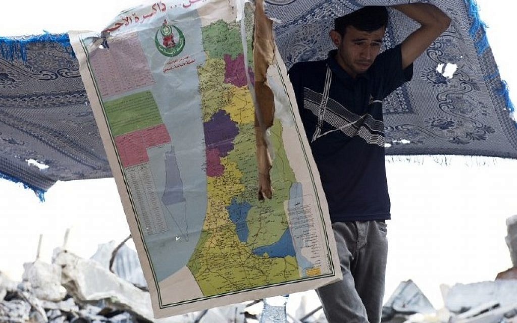 A Palestinian man is seen under a blanket and a map of Israel and the Palestinian Territories errected to give shade, as he walks over the rubble of what used to be a family home, in the Shejaiya neighborhood of Gaza City, on August 18, 2014.  (photo credit: AFP/ ROBERTO SCHMIDT)