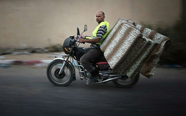 A Palestinian man drives his motorbike loaded with mattresses as he heads to a United Nations school to take refuge for the night in the northern Gaza Strip city of Beit Hanun, as a ceasefire between Israel and Hamas was due to end, on August 18, 2014. The ceasefire was later extended for another 24 hours. (photo credit: AFP/THOMAS COEX)