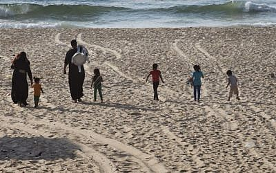 A Palestinian family walks towards the sea as they arrive to spend an afternoon on a beach in Gaza City on August 18, 2014. (photo credit:  AFP Photo/Roberto Schmidt)