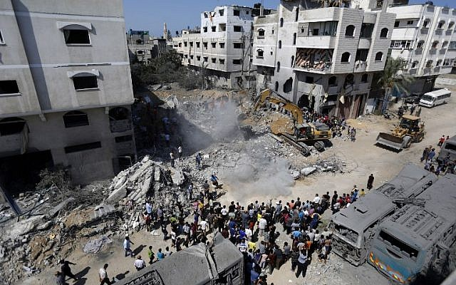 A digger removes cement and debris on August 20, 2014, of a home destroyed the night before in an Israeli airstrike on Gaza City's Sheikh Radwan neighborhood, targeting the elusive Hamas military chief Muhammad Deif (photo credit: AFP/Mohammed Abed)